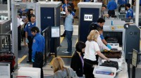 A man is screened with a backscatter x-ray machine as travellers go through a TSA security checkpoint in terminal 4 at LAX in Los Angeles