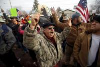 "A pro-militia supporter holds a constitution while chanting ""Hands up. Don't Shoot"" during a protest outside the Harney County Courthouse in Burns, Oregon"