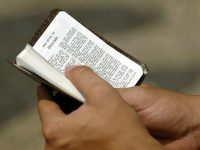 A-worshiper-holds-a-small-Bible-640x480